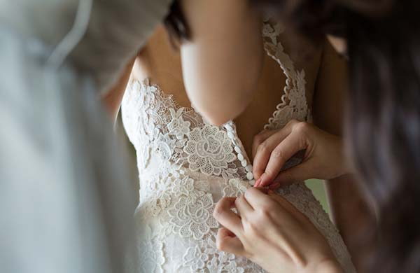 Bride getting buttoned up
