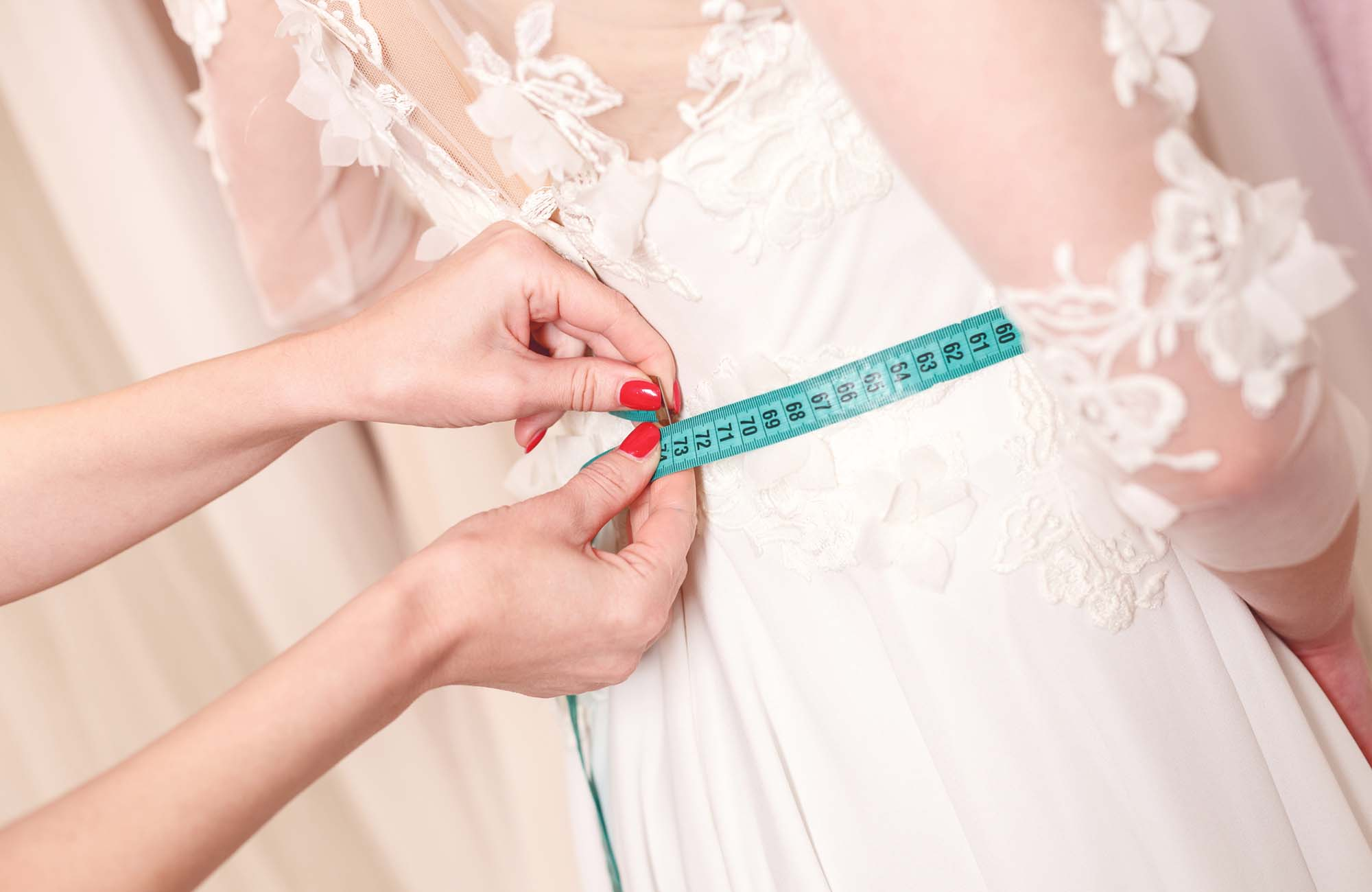 Skillful designer fitting bridal gown to girl